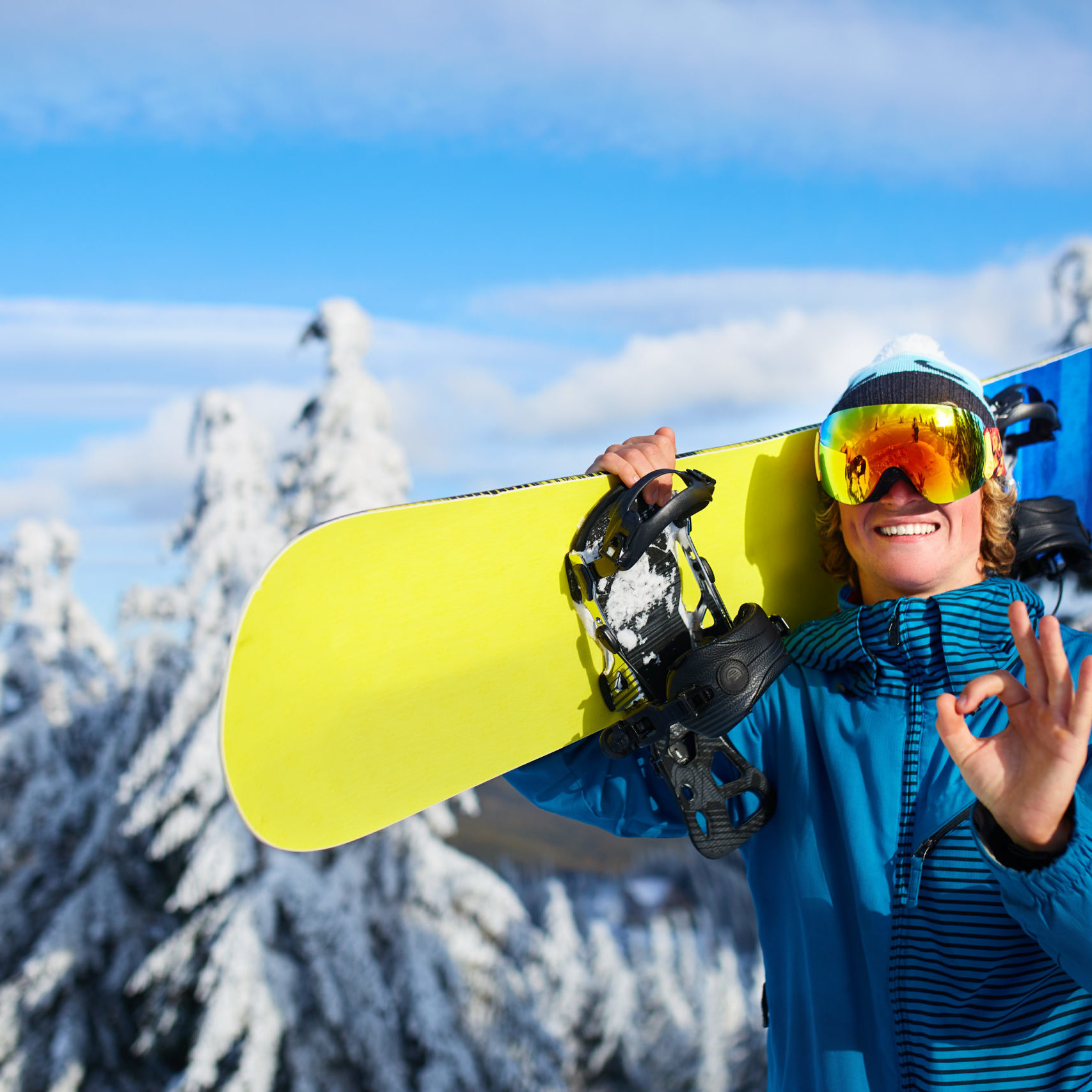 Smiling snowboarder posing carrying snowboard on shoulders at ski resort near forest before backcountry freeride and wearing reflective goggles, colorful fashion outfit. Rider showing OK sign. Modern snowboarding equipment.